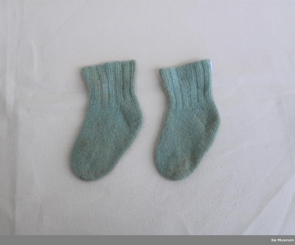 Ullsokkar til baby. Sokkane har hæl og ribbestrikk langs øvre kant.