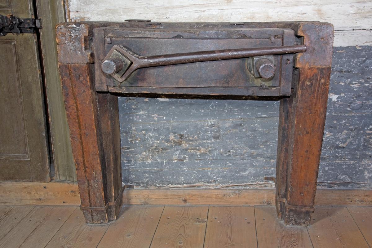 Press, skruvpress, av grova träbjälkar och med skruvar av järn fäst i väggen med järnbeslag. På pressens ovansida ett mellanrum, slits. I slitsen två träplattor för att pressa droger genom att veven av järn dras runt.