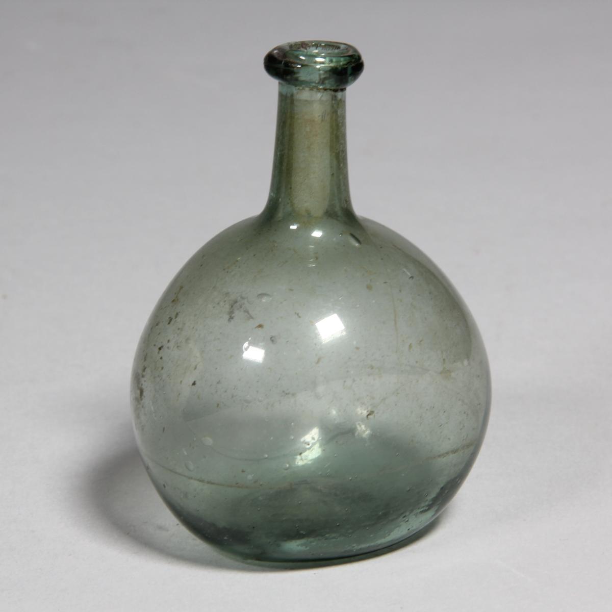 Flaska av grönt glas, rund med tillplattade sidor och hög hals.