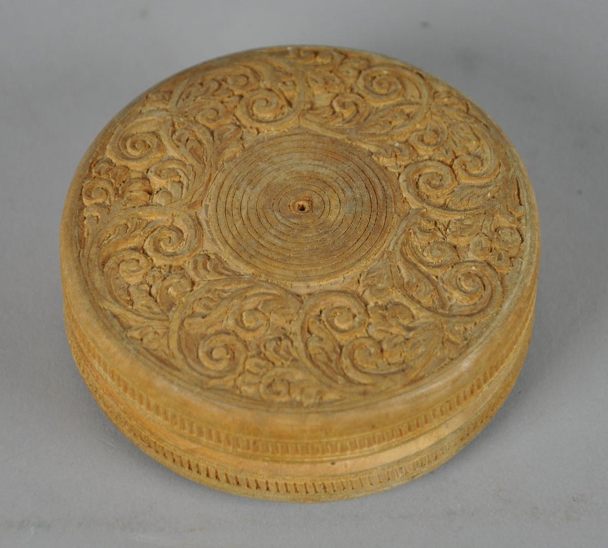 Rund eske av tre, med skjært dekor. På lokket er det skjært dekor med motiv av konsentriske sirkler med akantuslignende spiralformasjoner rundt. På sidene er det border med rettvinklede linjer inni.  Spor fra teipbit på undersiden.