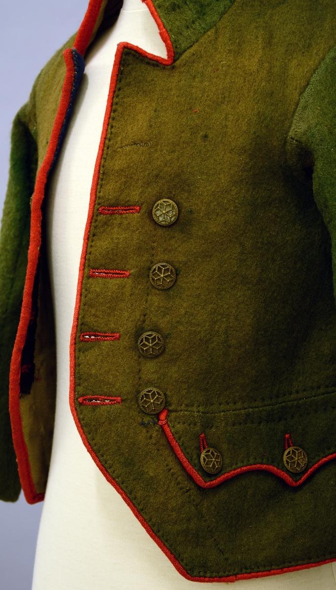 Herretrøye. Fra protokollen: Tröie og vest til mandsdragt. Tröien er grøn med rød kanting, har höi krave og lommer med store klaffer, gjennembrudte messingknapper.