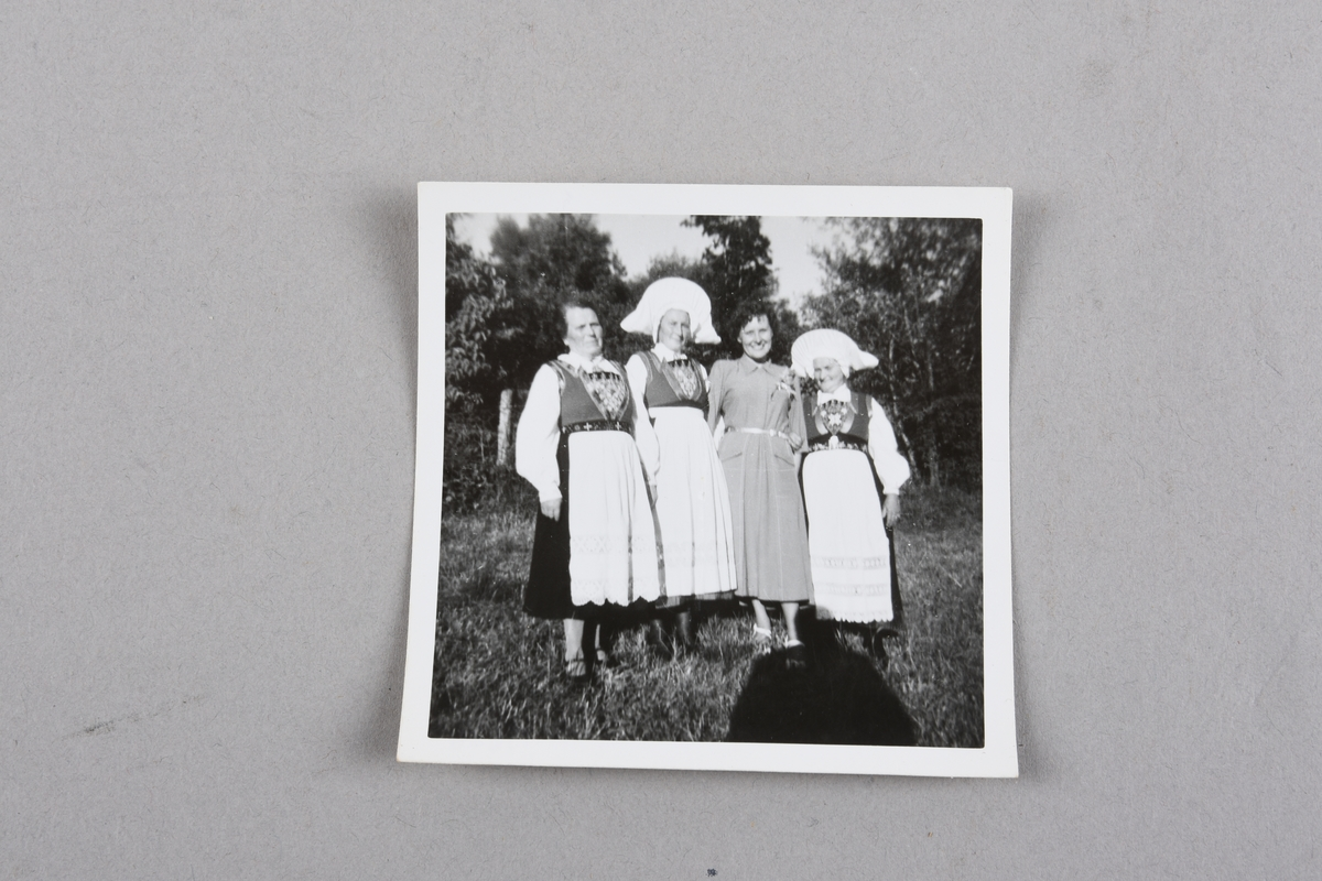Sorthvitt fotografi av fire kvinner utendørs på gressplen med trær i bakgrunnen. Tre er iført Fanabunad, to av dem med hodeplagg. Den fjerde er iført pen kjole og lyse sko. Skyggen av fotografen vises i forgrunnen til venstre.