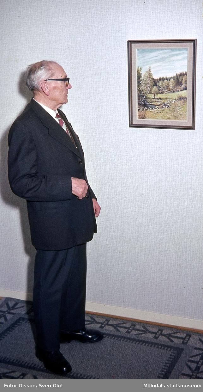 """Konstnären Knut Berg (24/11 1881 - 17/1 1983) fotograferad vid en av hans tavlor i bostaden på Vänortsgatan 12 D i Mölndal, den 26/2 1966. Foto i samband med att Knut intervjuades av Sven Olof Olsson. Denna intervju blev bakgrunden till boken """"Mölndal i färg: Knut Bergs tavlor och Sven Olof Olssons fotografier""""."""