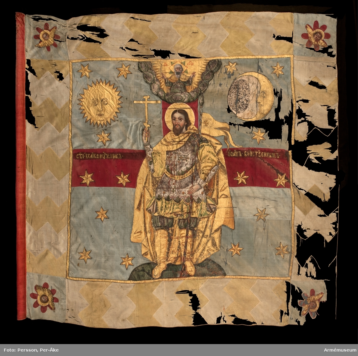 Fana av den typ som användes av streltserförband. Duk av sidentaft. Blått huvudfält som avdelas av ett rött kors. Bård i gult och benvitt zig-zag mönster. Blå fyrkanter i varje hörn med en ängel med guldvingar omgiven av röda blomblad. Fanans huvudmotiv är den helige Johannes soldaten omgiven av solen, månen och 16 stjärnor. På korsarmarna anges helgonets namn på ryska. I ett moln över huvudet på Johannes är en avbildning av Gud. Målat övervägande i guld- (äkta guld) och silverfärger (blyvitt). Strumpa av rött linne. Stång av standartyp, avsågad. Bemålad med blomsterornament. Spår finns av äpple som dock saknas.