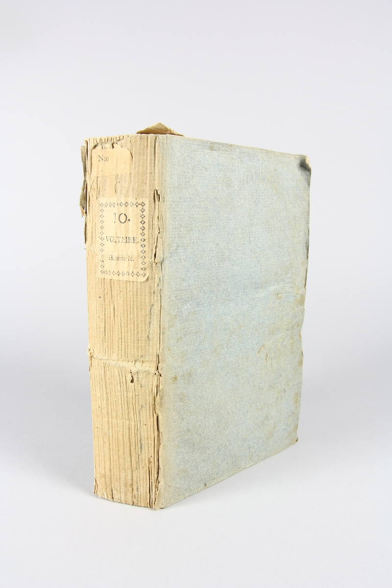"""Bok, häftad,""""Oeuvres complètes de Voltaire"""", del 10, tryckt 1785, (titelblad saknas). Pärm av gråblått papper, på pärmens baksida klistrad sida ur annan bok. Med skurna snitt. På ryggen klistrad pappersetikett med tryckt text samt volymens nummer. Ryggen blekt."""