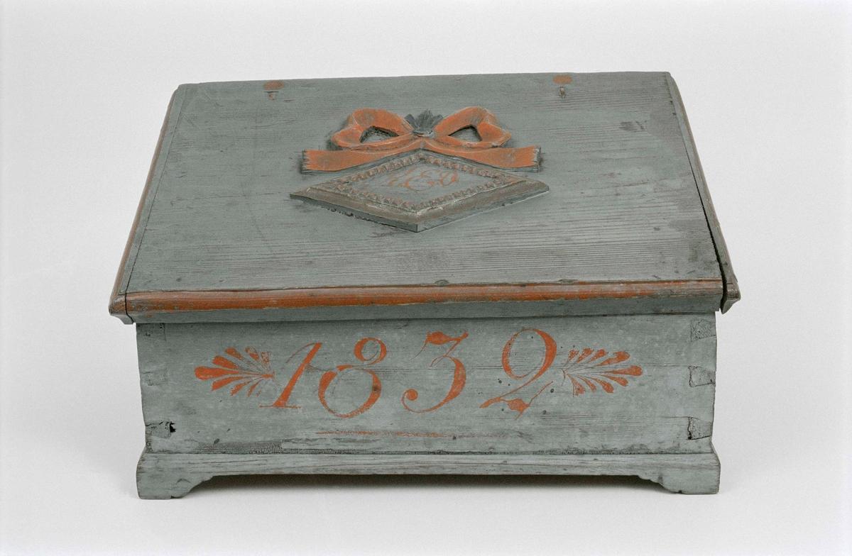 """Skrin av furu med pulpetlock, målad blå med röda lister, två mindrefack innuti. Sinkade sidor. På locket skuren rosett i hög relief samt skuren romb med initialer """"KED"""". Skrinet märkt """"1832"""". Skrivet med blyerts på lockets insida: """"1862,1864, Erik Eriksson"""""""