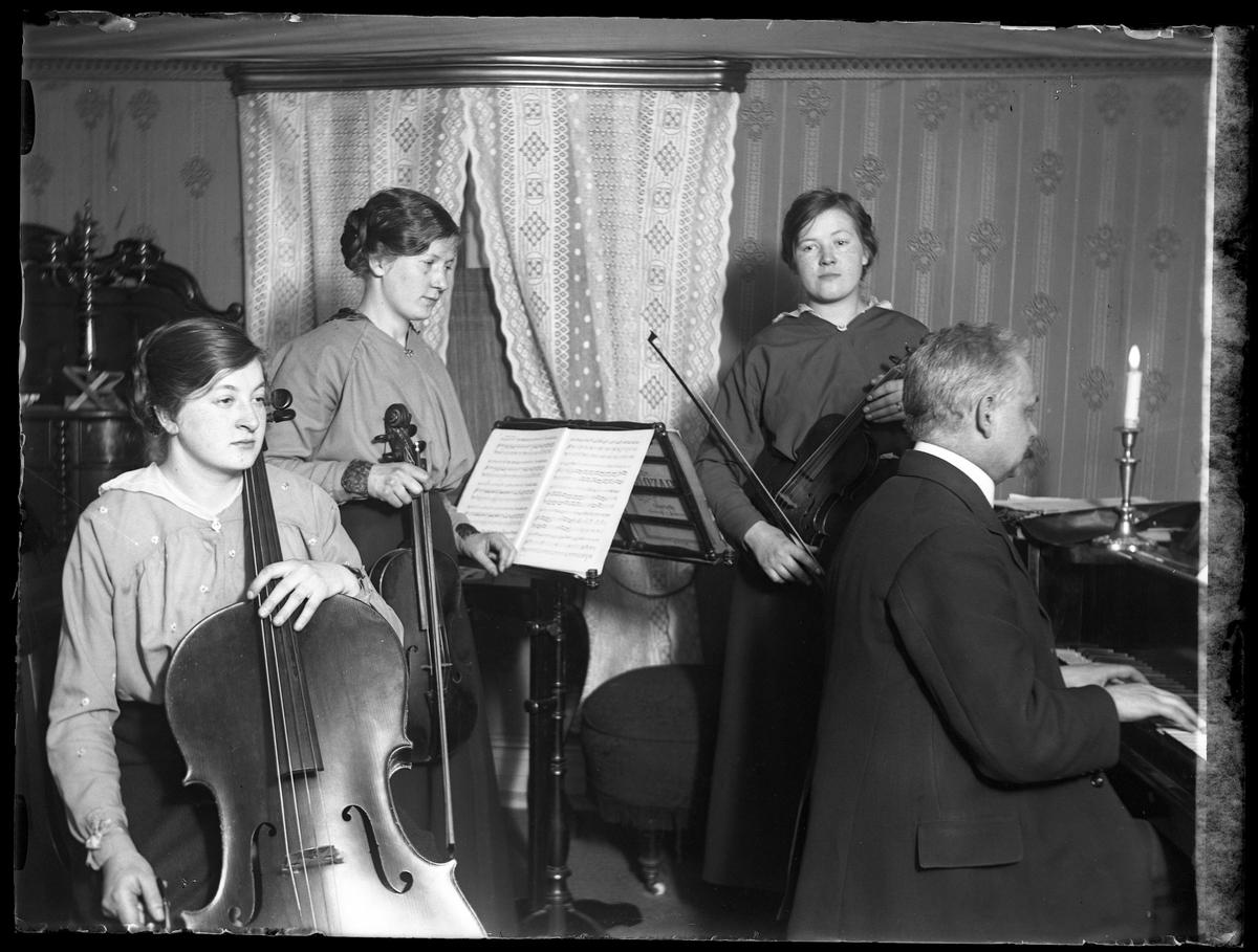Anna, Eva & Edith Claesson och far (troligen fotografen Harald Olssons far) spelar fiol, cello och piano.