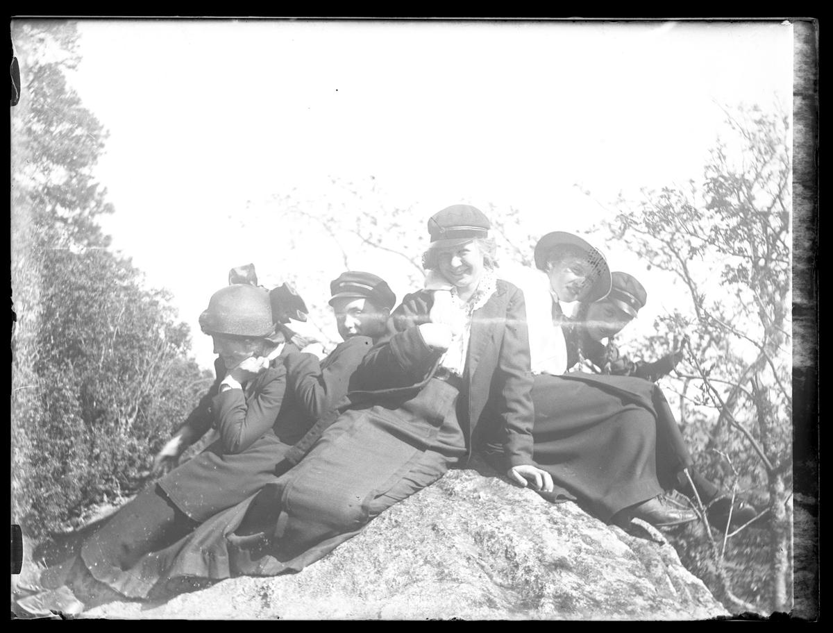 """Fem flickor poserat på en sten i skogen. I fotografens egna katalog står antecknat """"6:e klassens flickor""""."""