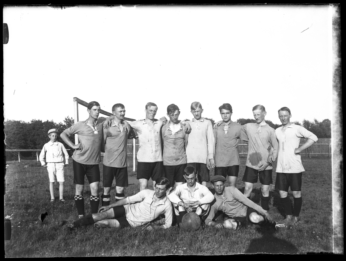AIFs (Alingsås Idrottsförening) I:sta fotbollslag håller om varandra. Bredvid dem står en liten pojke.