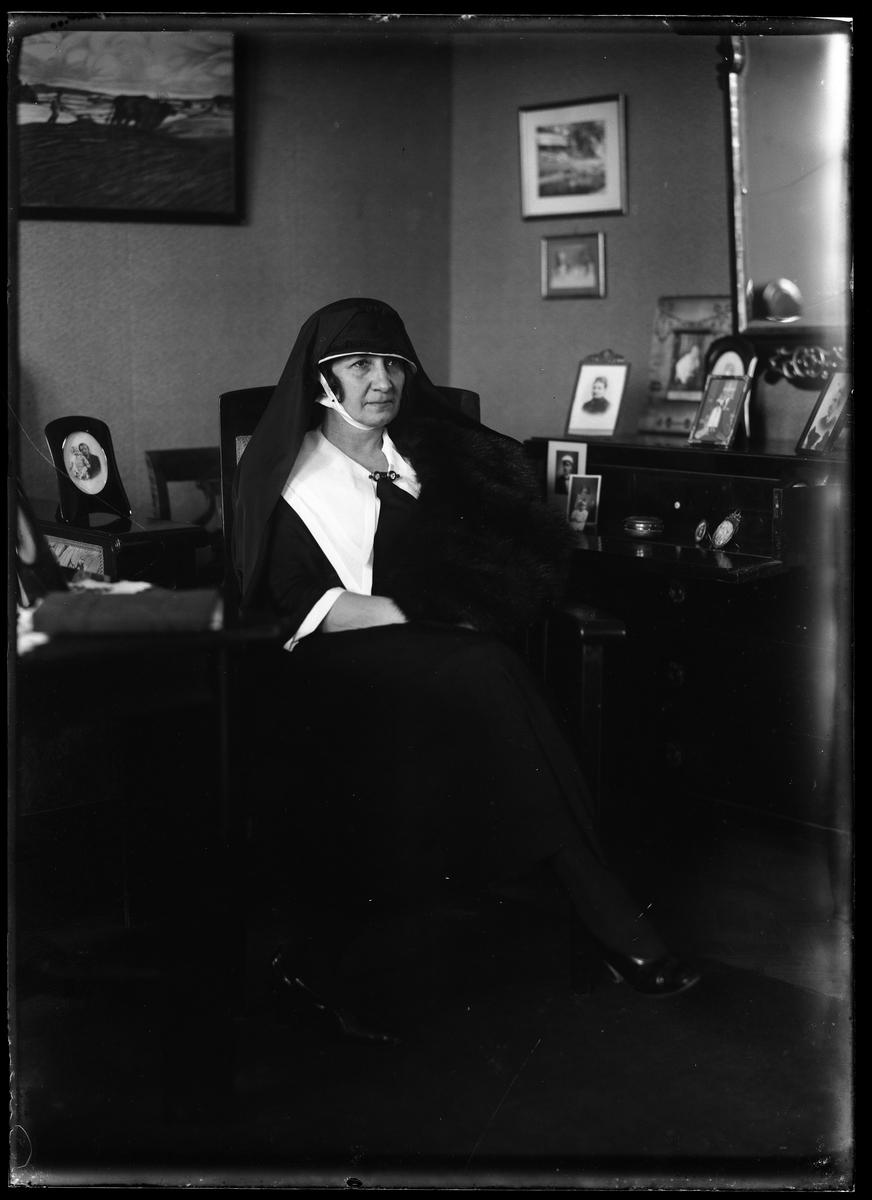 Fru Lenander porträtterad klädd i svart och vitt med huvudbonad och långt flor, möjligen i sorg.