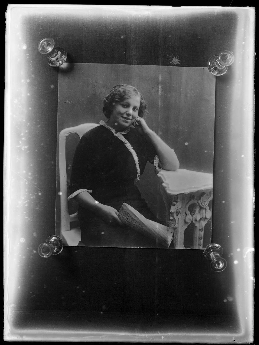 Reprofotografi av porträtt av okänd kvinna med tidning i handen sittandes vid ett bord.