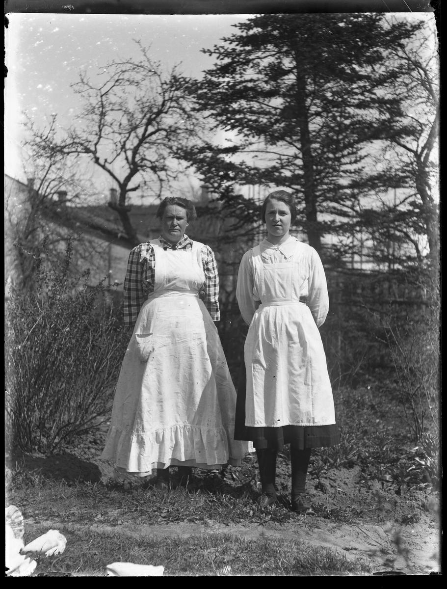 Anna Glasin och Hedvig iklädda förkläden och med händerna på ryggen fotograferade utomhus. I bakgrunden skymtar byggnader mellan träden.