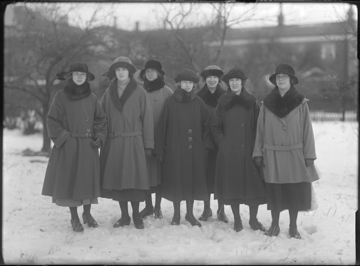 Gruppbild med sju kvinnor klädda i vinterkappor och hattar fotograferade ute i snön. Längst till vänster står Lilly Johansson och kvinnan tredje från höger heter Lisa (efternamn okänt).