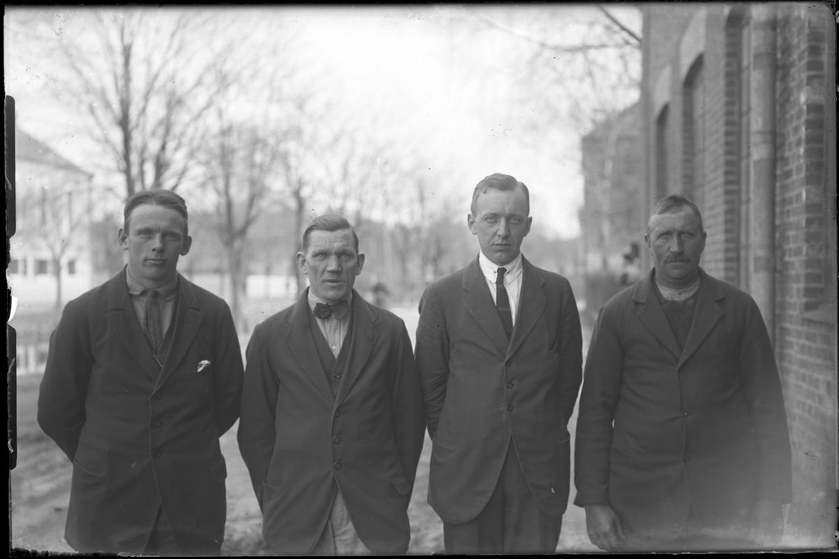 """Fyra män står på rad utanför Alingsås Bomullsväveri. I fotografens katalog står: """"Hallgren, Werner & Strandberg""""."""