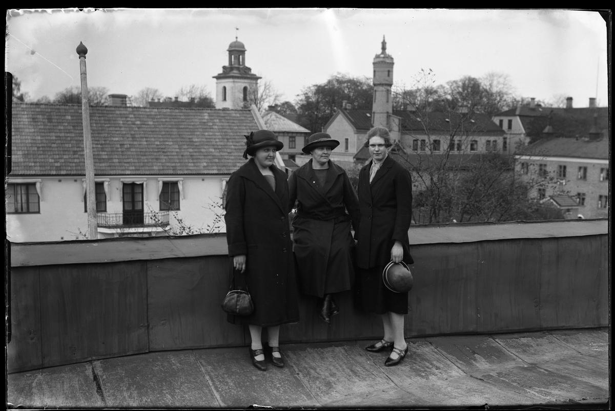 """Tre kvinnor porträtterade på en balkong eller en takterrass. Den äldre kvinnan sitter på räcket och håller om de yngre som står på var sida om henne. I bakgrunden syns stadskyrkans torn och Väktaregårdens slangtorn. I fotografens egna anteckningar står det """"Fru Johansson med dotter""""."""