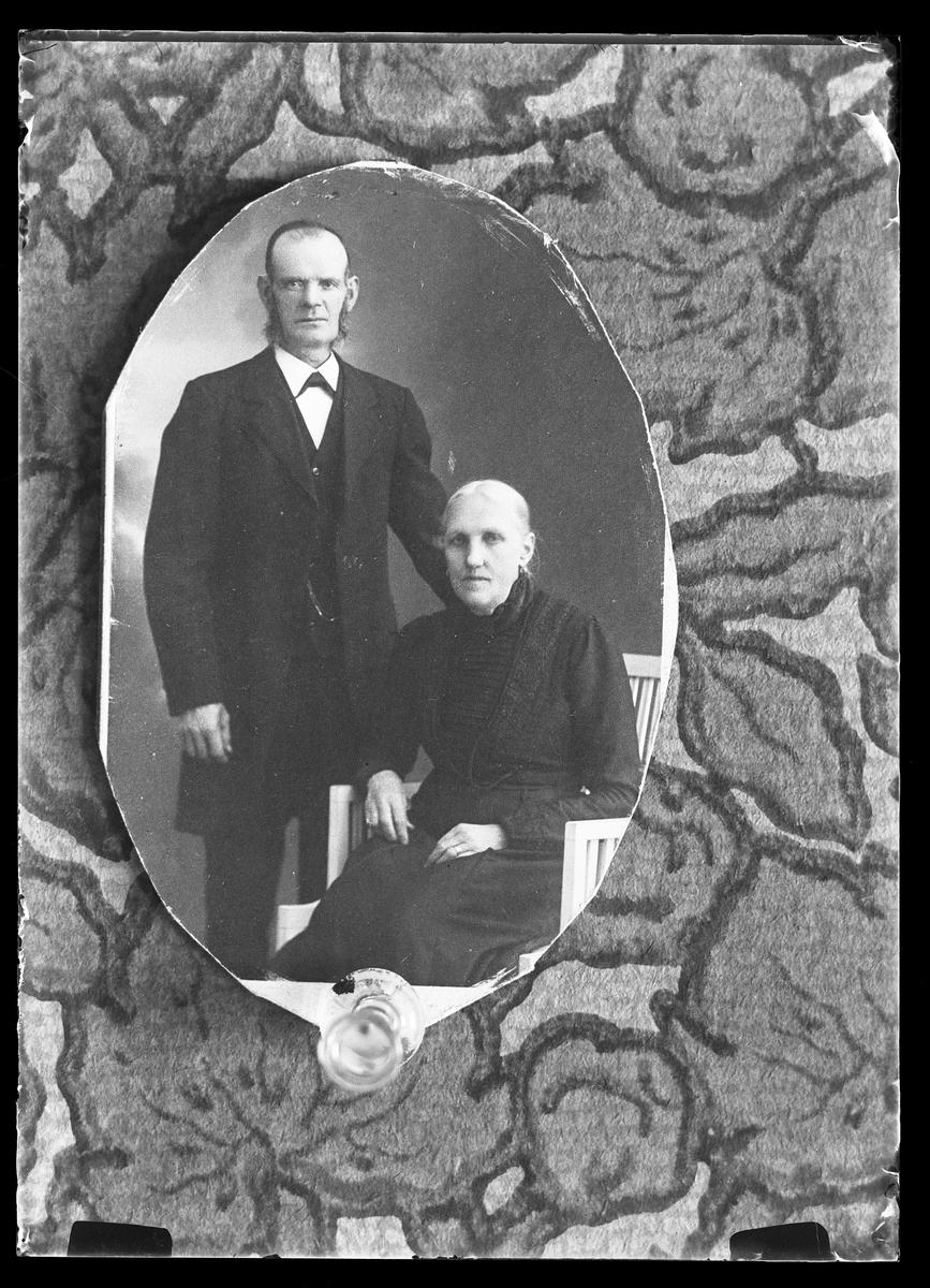 """Reprofotografi av porträtt på ett äldre svartklätt par. I fotografens egna anteckningar står det """"Rep. för Hj. Nilsson"""". Tolkat som Hjalmar Nilsson."""