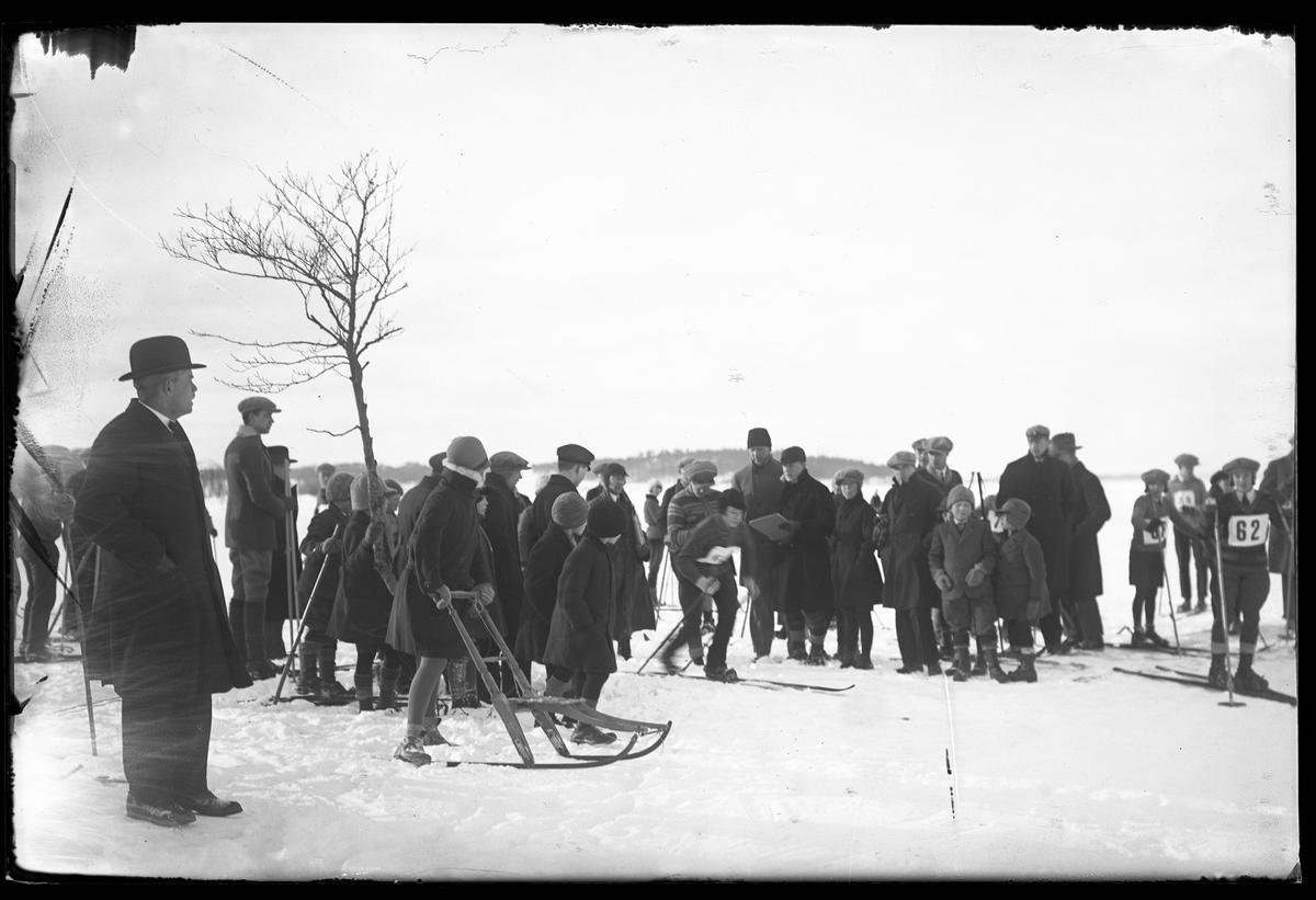 Åskådare och tävlande fotograferade vid starten av en skidtävling.