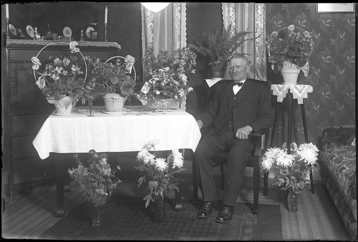 Alfred Andersson fotograferad i ett finrum omgiven av blommor i samband med sin 75årsdag.