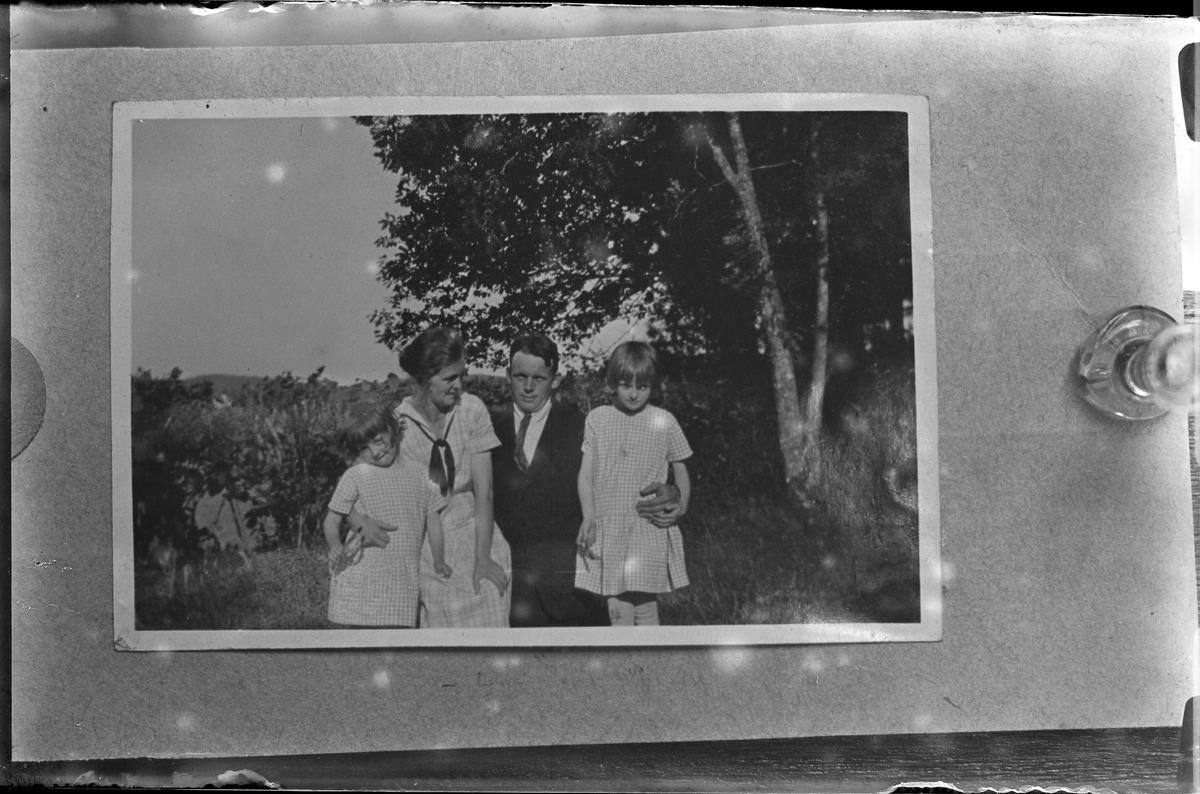 """Reprofoto av bild på en kvinna, en man och två barn fotograferade utomhus. Kvinnan och barnen bär rutiga sommarklänningar medan mannen har kostym. I fotografens egna anteckningar står det """"Rep. för Strandberg""""."""