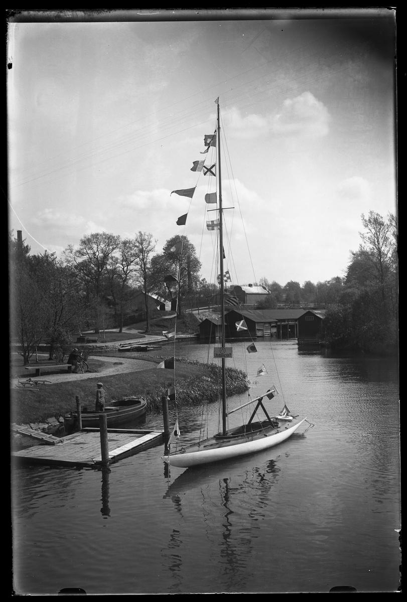 Alingsås Segelsällskaps (A.S.S) utlottningsbåt ligger förtöjd vid en flytbrygga. Vid strandkanten står en man i en annan båt och på en parkbänk uppe på land sitter en man med en cykel.