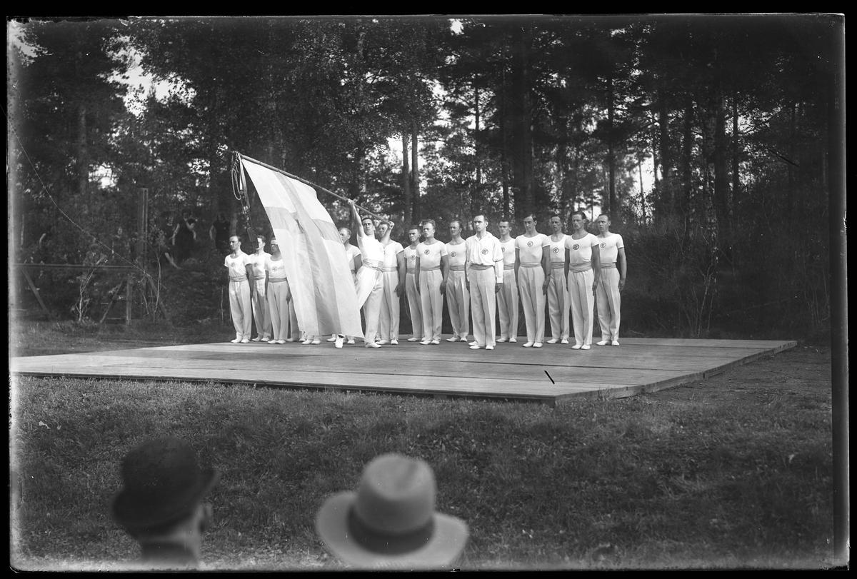 Gymnaster från Alingsås Idrottsförening (AIF) står uppställda i Parken. Den ena mannen håller en stor fana och i förgrunden syns två åskådare i hatt.