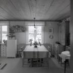 I köket på gården Sunnanåker finns ett köksbord och ett kylskåp samt väggprydnader, januari 1970.