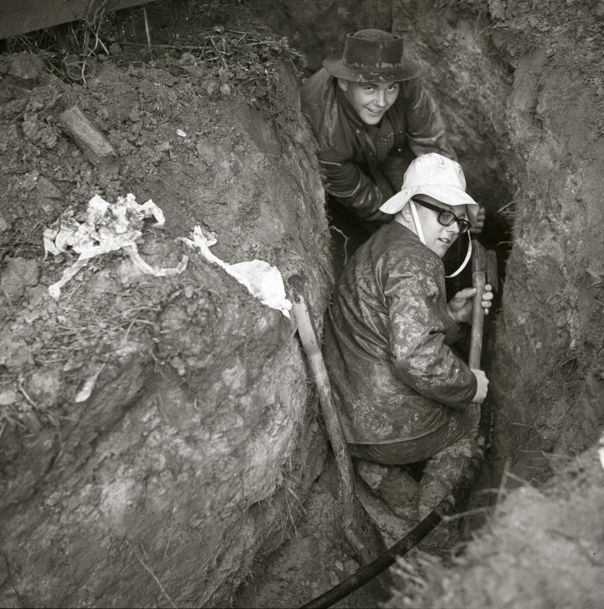 Två män gräver ett dike för ledningar och slangar till ett hus vid gården Sunnanåker, 1967.