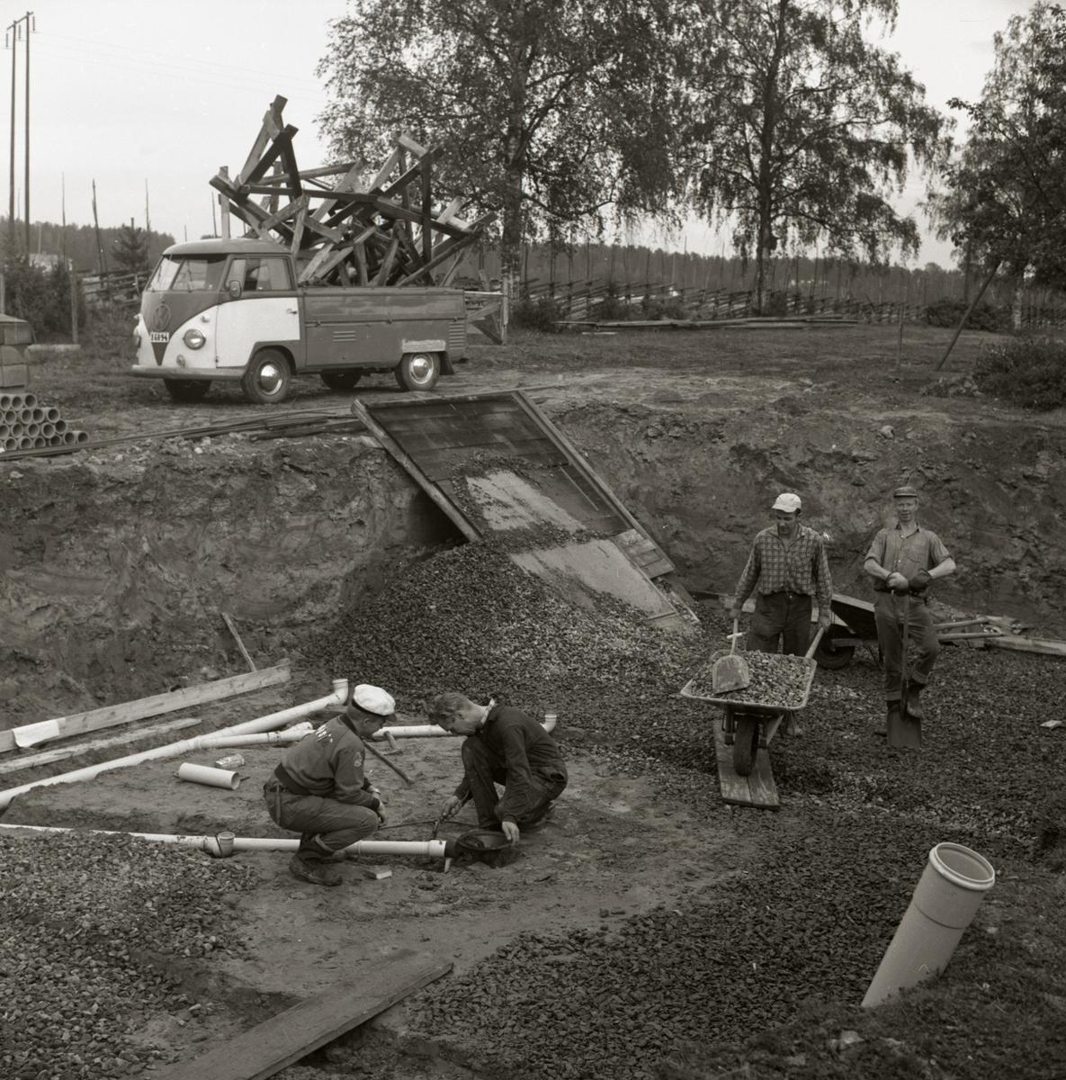 Två män lägger rör i en husgrund och två andra män fyller grunden med grus vid byggnation av bostadshus vid gården Sunnanåker, 1967.