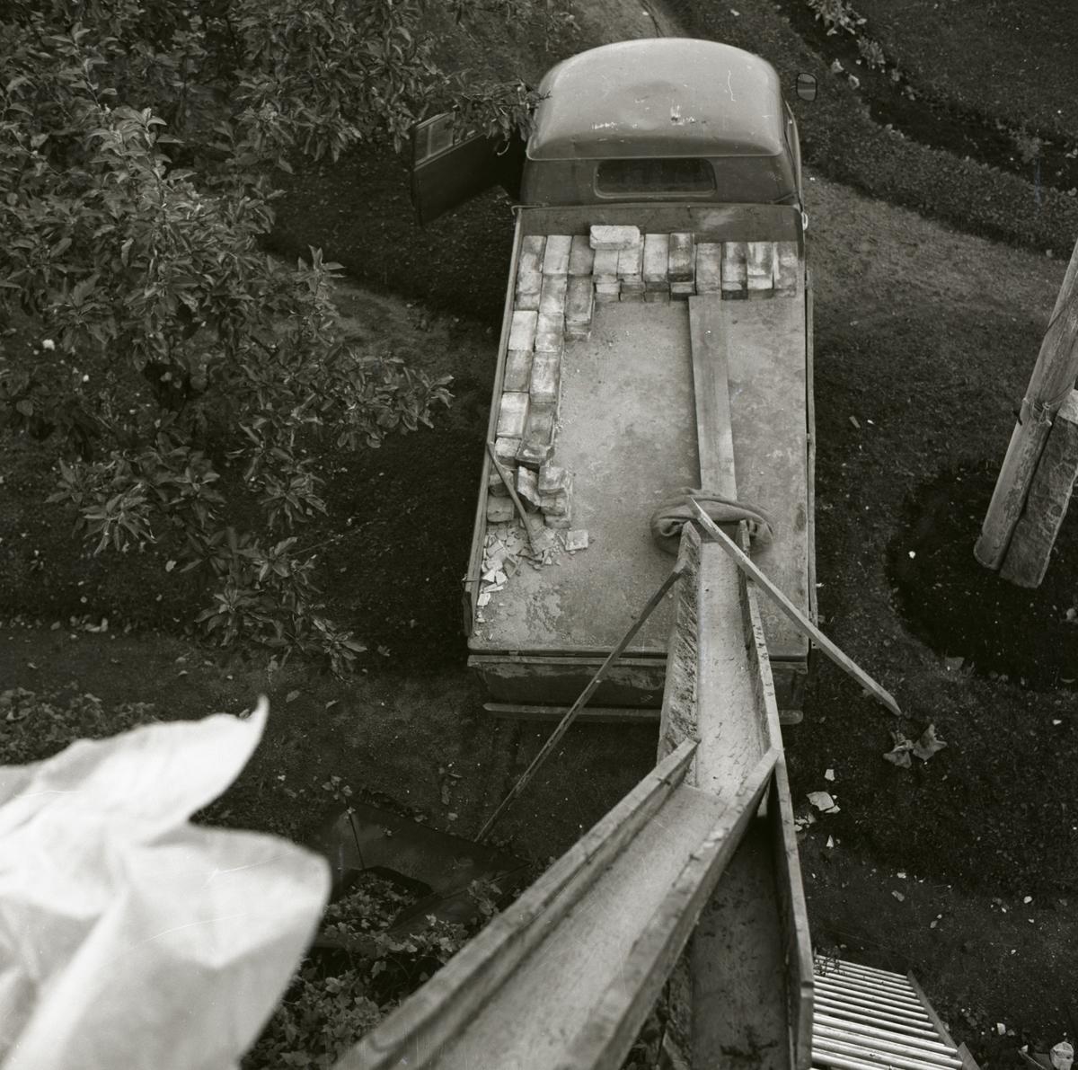 En ränna leder ned till ett bilflak på vilket tegel ligget staplat, 1967.