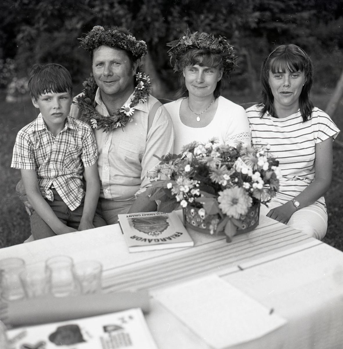 """En familj sitter vid ett bord med duk, blombukett, glas och boken """"Friargåvor"""" den 30 juli 1982. Några av dem bär blomkransar på huvudet."""