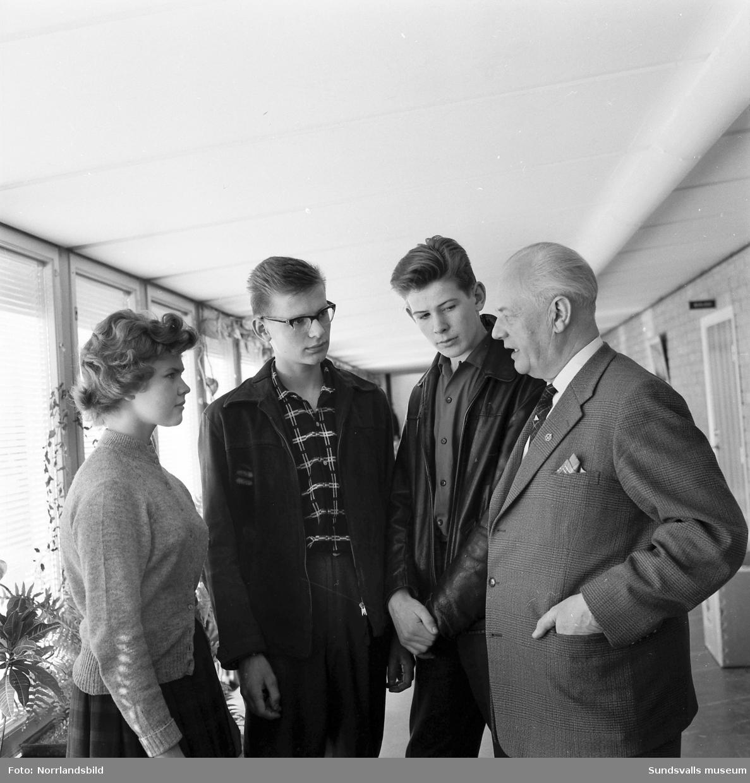 Tre ungdomar från Enok ungdomsförening samtalar med en äldre man, eventuellt i en skolkorridor.