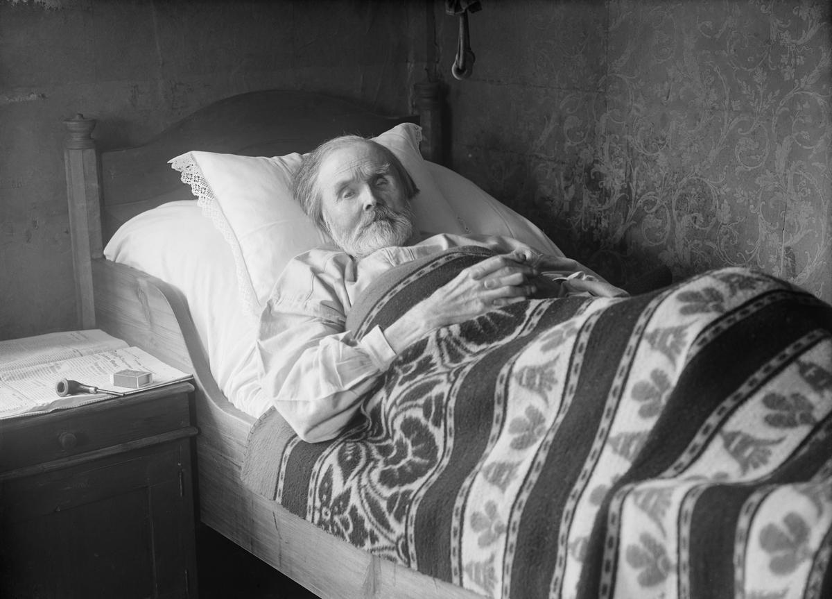 Mann ligger i seng, antakelig på Bådstø, Tretten, eller i nærheten