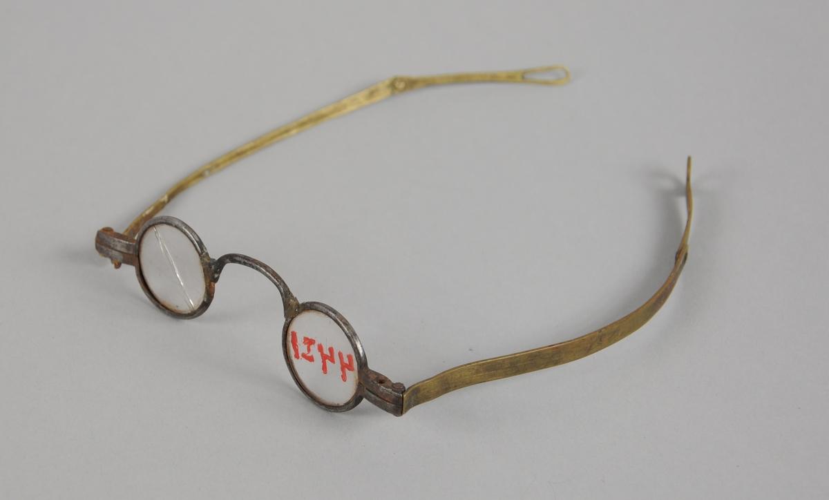 Briller med små ovale brilleglass og metallinnfatning. Brillestengene kan brettes ut.