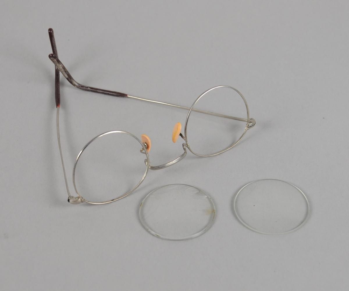 Brillerinnfatning av metall med plast ytterst på brillestengene. Innfatningen ligger i et etui, der det også ligger et par runde brilleglass som ikke passer til innfatningen.