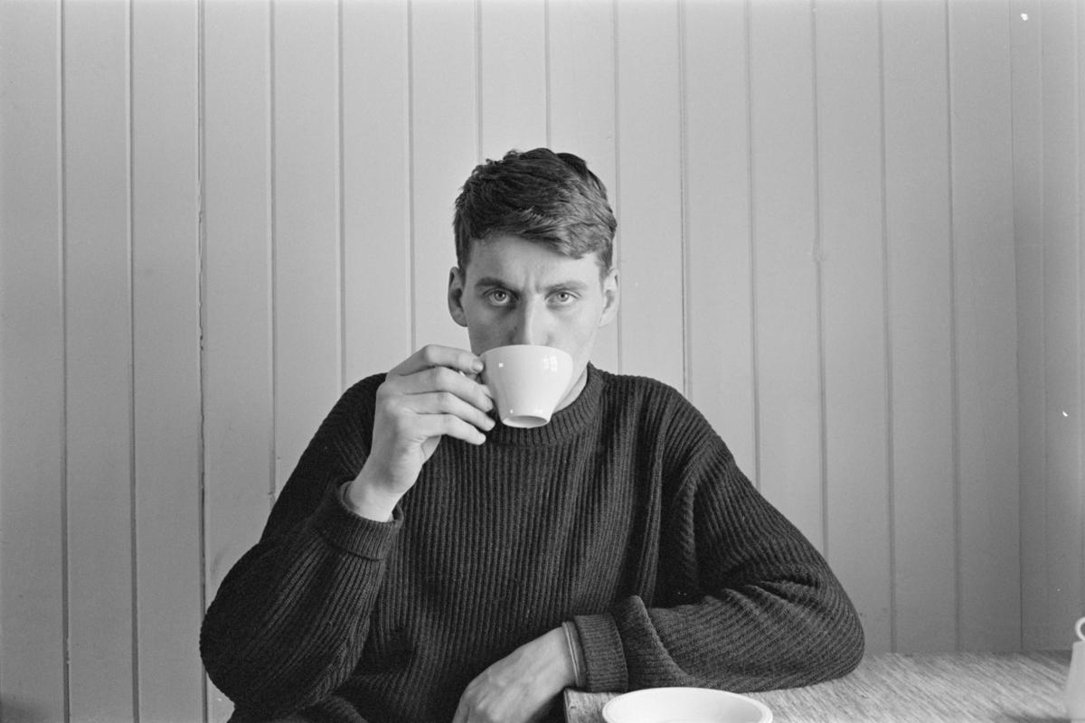 En mann sitter ved et bord og drikker kaffe.
