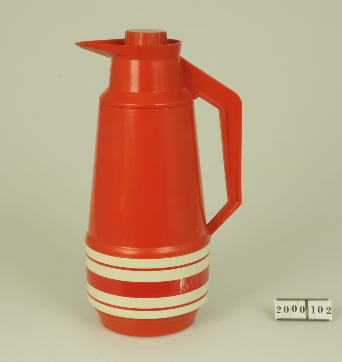 """Röd termos av plast med vita dekorränder på nederdelen. Skruvkork och handtag i sidan.  Modell: """"Dacapo"""""""