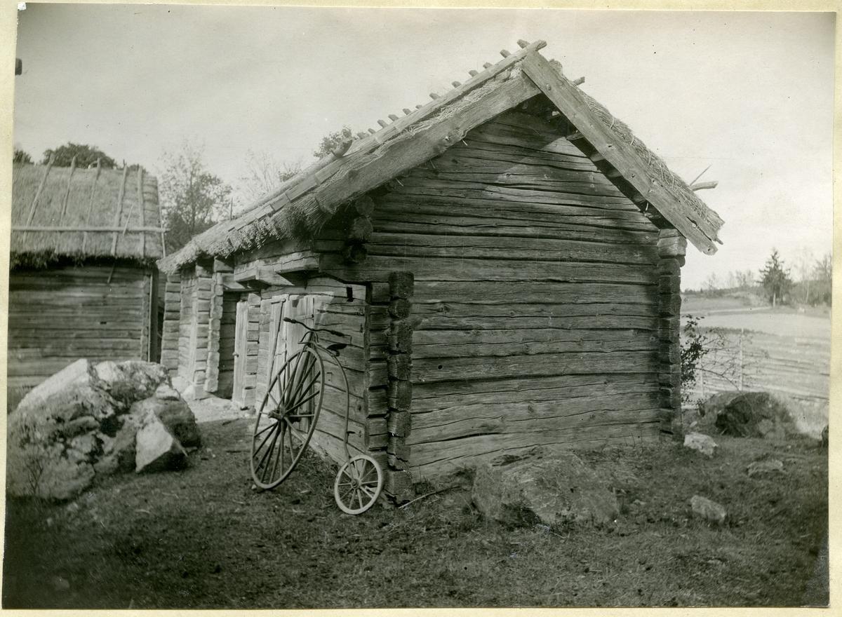 Gunnilbo sn, Gunnilbo by.  Uthus med halmtak. Gammaldags cykel står lutad mot väggen.