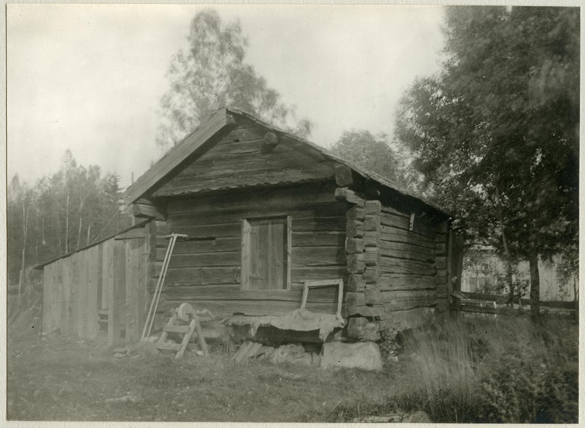 Gunnilbo sn, Gunnilbo by.  Uthus. Slipsten står framför byggnaden och en räfsa i trä står lutad mot väggen.