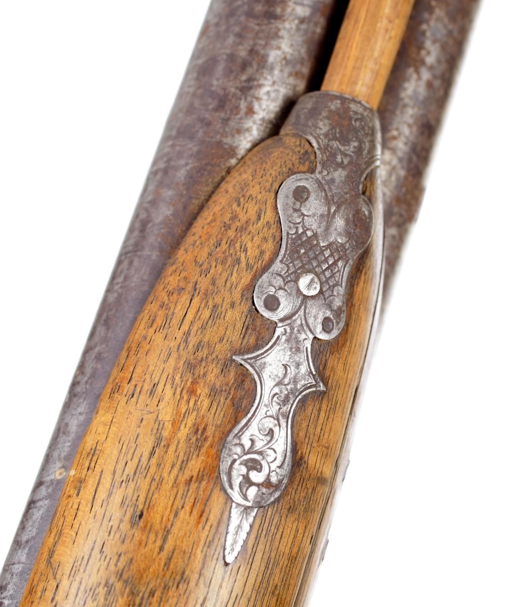 Dubbelpipigt jaktgevär försett med slaglås. Kolv och stock är fernissade och saknar dekor. Låsbleck, varbygel, hanar och bakplåt är graverade med bladmotiv. Kolven har en slät bakplåt, förutom delen som går upp över kolvryggen, som är graverad. Kolven har en slät kolvhals och fäste för bärrem i underkanten. Laddstocken sitter i tre rörkor, varav den mellersta har en byglel för bärrem. Geväret är försett med ett filat gropsikte och korn i mässing placerat mellan piporna strax bakom mynningarna. Piporna är damaskerade och runda i utförandet, och slätborrade med en innerdiameter på ca. 17 mm. Inskrivet i huvudkatalog 1969.