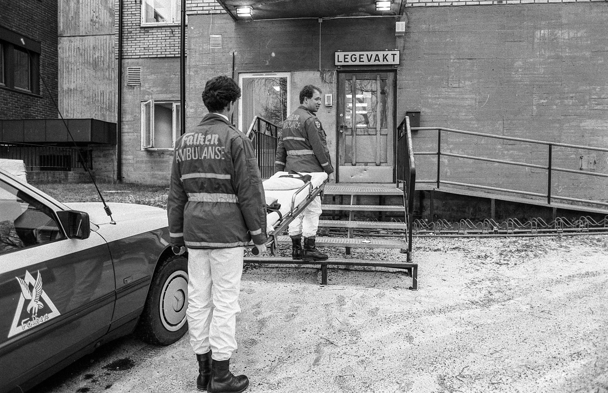 Legevakten i Ski / Oppegård ved Ski sykehus. Ambulansepersonell, Roy Pedersen og Frank Rødsand, fortviler, står med båre mellom seg utenfor på en jerntrapp.
