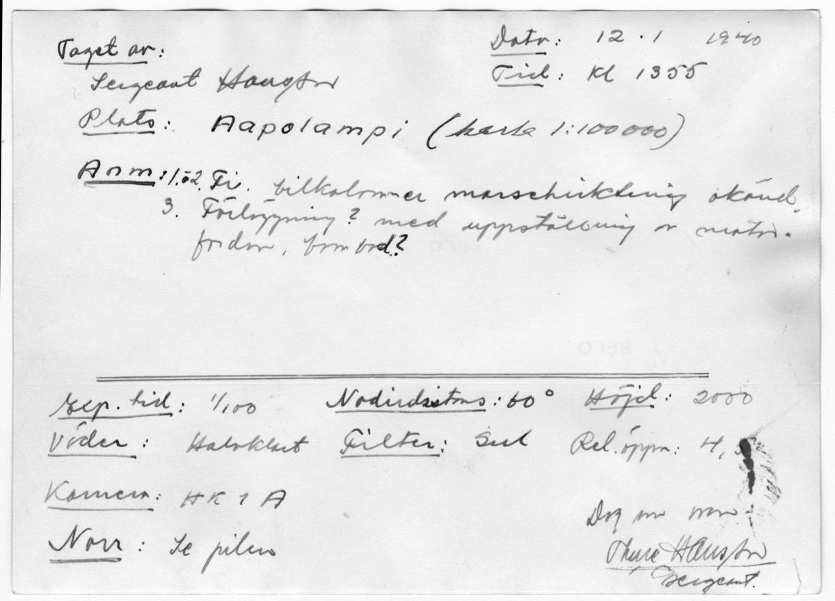 Flygfotografi av landskap vid Aapolampi i norra Finland under finska vinterkriget, 1940. Spaningsbild över skog, väg och fält tagen av flygare vid F 19, Svenska frivilligkåren i Finland. Längst till vänster i övre kant syns en finsk bilkolonn längs vägen.