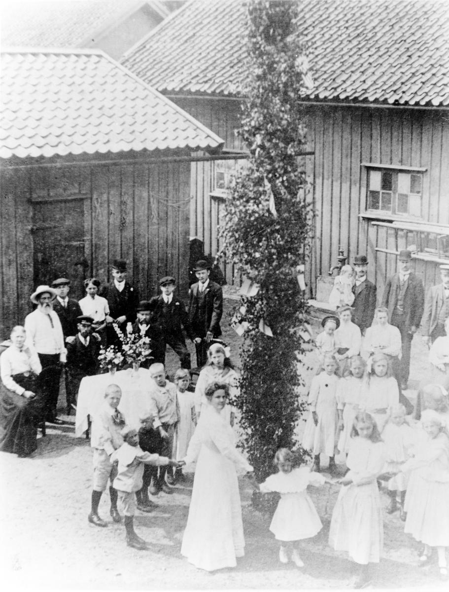 Kvarter Spinnaren. Spinnaregården. Midsommarfirande. Mannen till vänster med vitt skägg och vit hatt är dressare Persson, hans dotter har kommit från Amerika, (kvinnan längst fram bland barnen.) Den så kallade Spinnaregården revs 1967 för att ge plats åt nuvarande kvarter Hill.