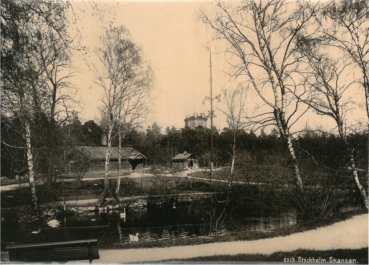 Morastugan med den lilla Hackstugan till höger, Skansen. I förgrunden fågeldamm, i bakgrunden syns tornet Bredablick.