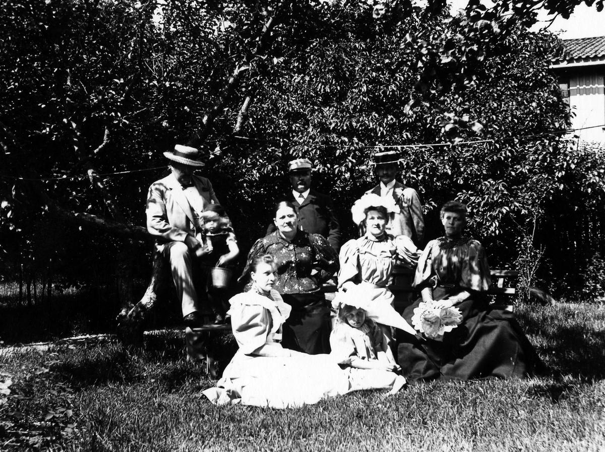 Gruppbild på tre män, fyra kvinnor och två barn som sitter i en trädgård, kvarteret Gustav.