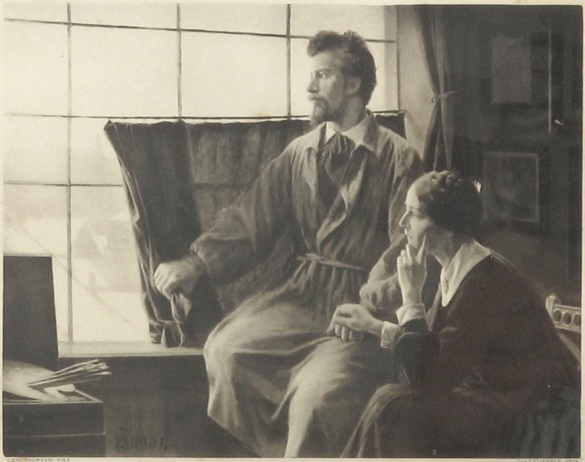 Atelier med maleren og hans hustru foran vinduet. Mannen drar gardinen til side, og de kikker begge ut av vinduet.