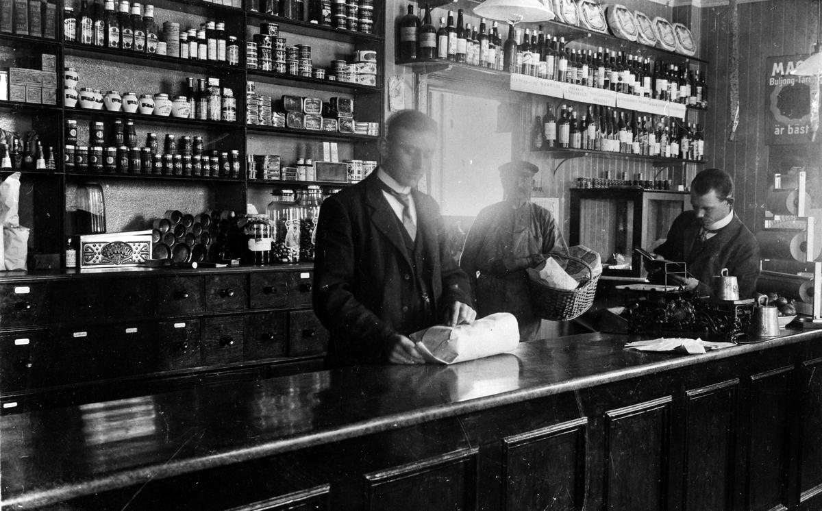 Bild tagen i Larssons Speceriaffär med 3 män bakom disken. Lars Johansson t.v. slår in något i papper, mannen i mitten står med en stor flätad korg och t.h. syns affärens ägare C Th Larsson som läser i en bok. Affären etablerades 1885 av J F Welin, som ännu var ägare 1906 (Älvsborgs läns kalender 1906). 1911 övertogs firman av C Th Larsson som ännu var ägare 1923 (Skaraborgs och Älvsborgs kalender 1923).