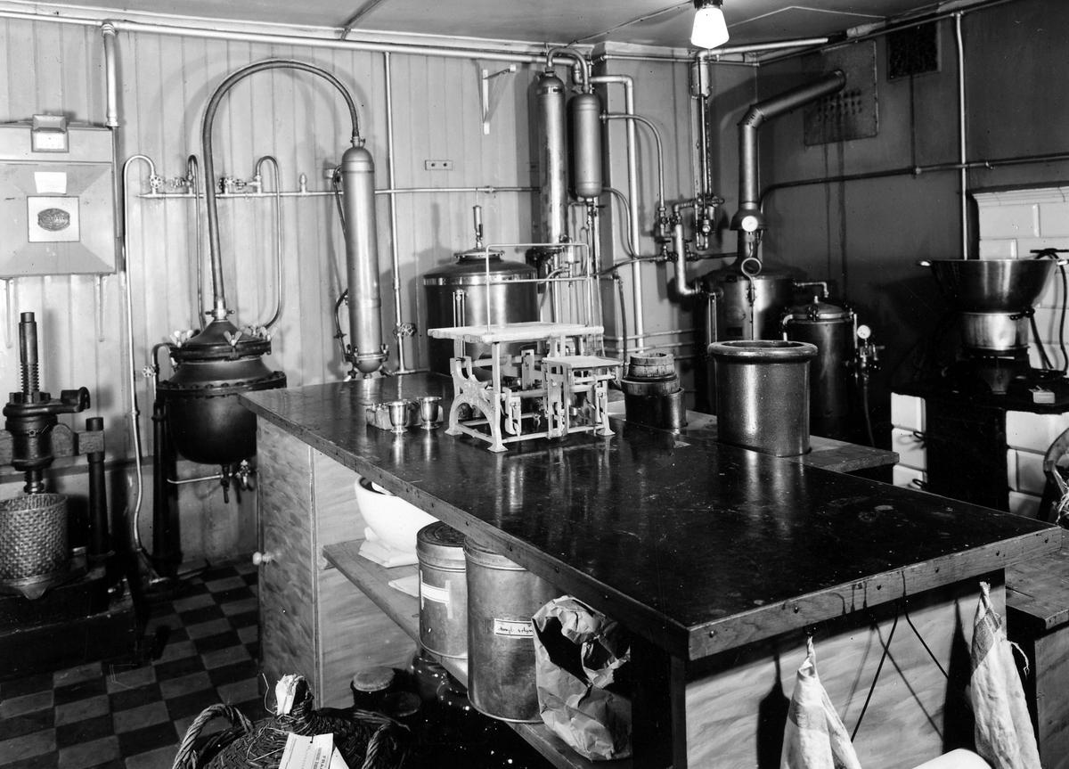 Bilden visar laboratoriet på apoteket Hjorten. Rummet är fyllt med olika maskiner som apoteket anväde för tablettillverkning och/eller andra ändamål.