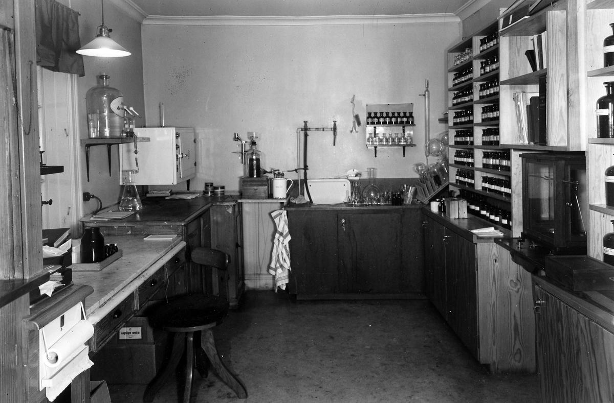 """Ett av arbetsrummen i apoteket Hjorten. Rummet kallades """"Analysen"""". Till höger hyllor med glasflaskor, mitten provrör och provrörställningar och till vänster en arbetsyta."""