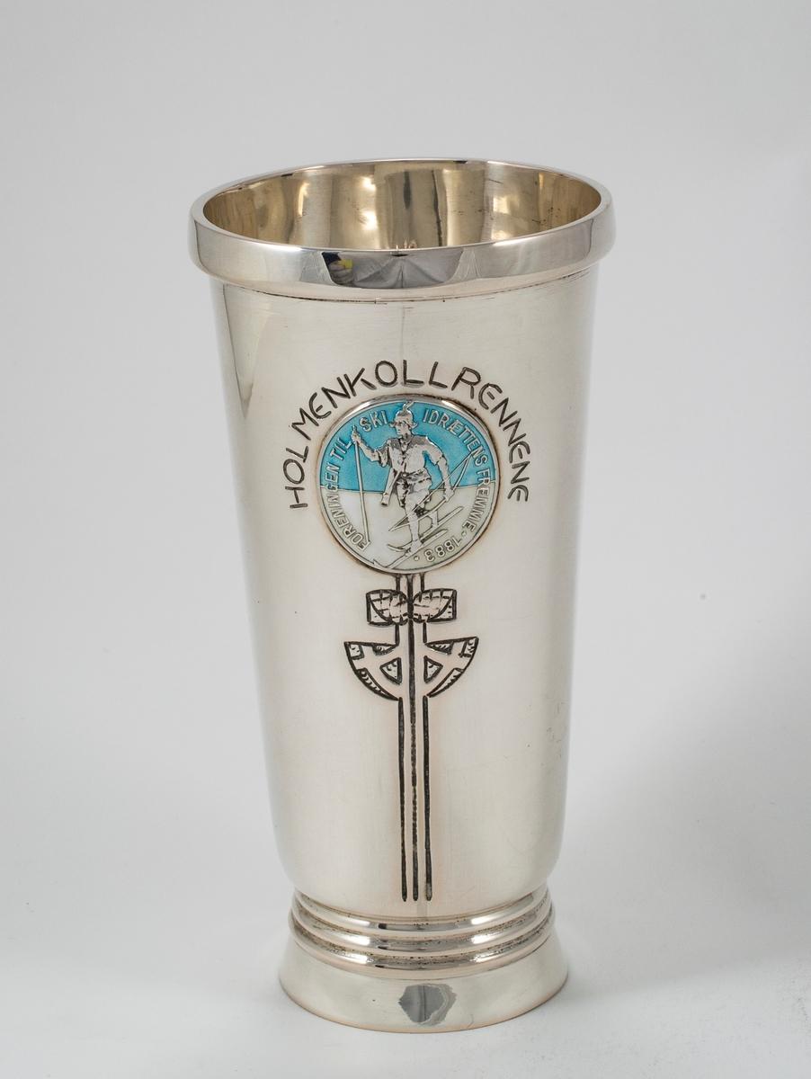 Sølvpokal med Skiforeningens emblem i blått og hvitt.