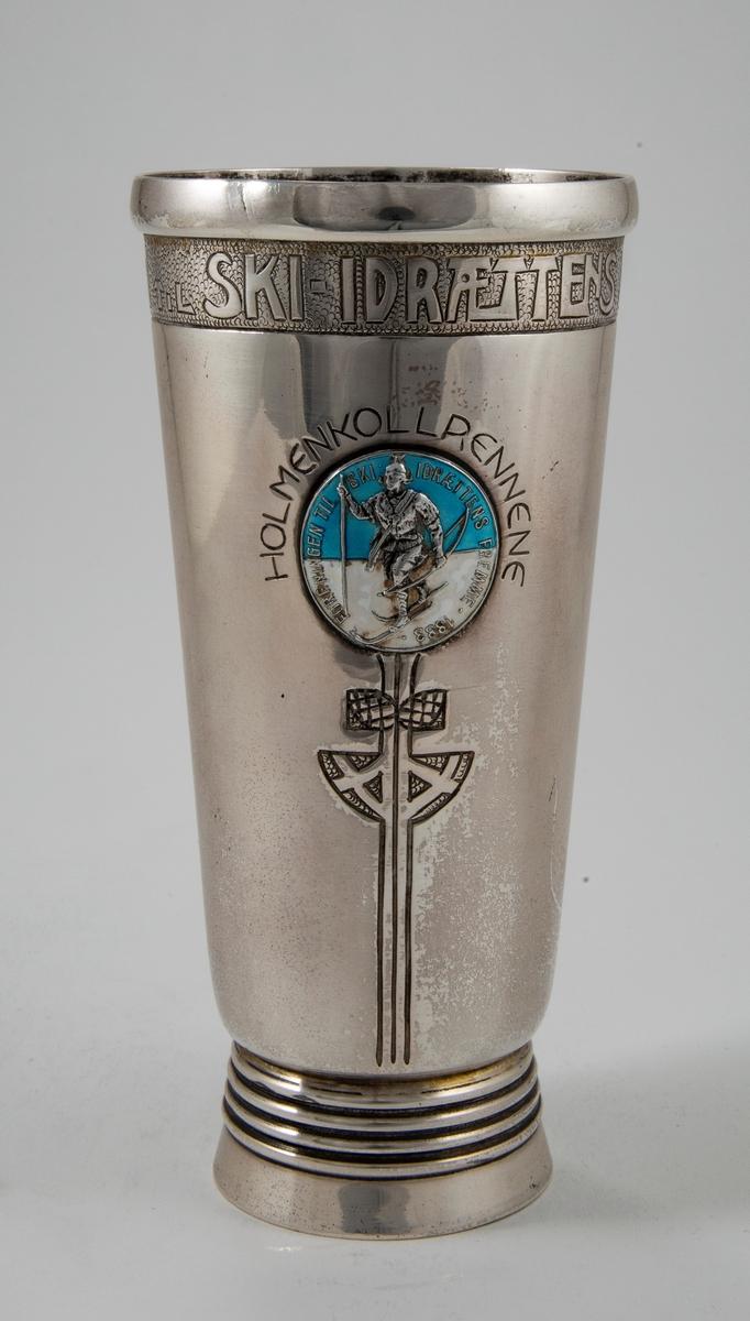 Sølvpokal med Skiforeningensemblem i blått og hvitt.